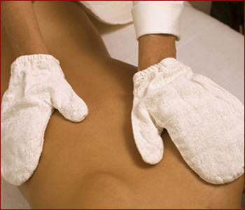 Young woman receiving massage, mid section